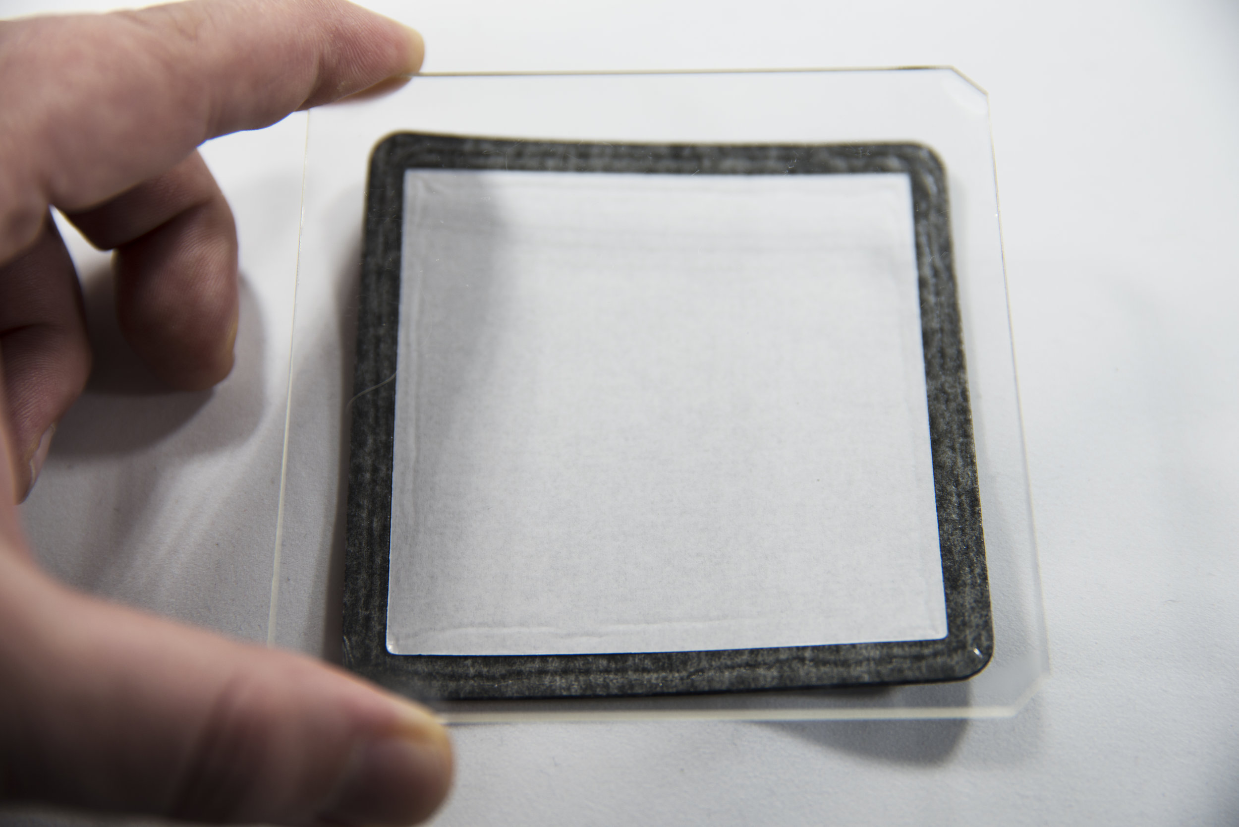 """Visually align the filter above the gasket with the etching on the filter facing upwards and using two hands (I needed a hand free to press the shutter in the shot above) place the filter squarely onto the gasket.  Instinct will tell you to start at one end and """"roll"""" the filter on to the gasket. The problem with this approach is that if you feel the alignment isn't quite right, you will not easily be able to unstick the gasket and start again."""