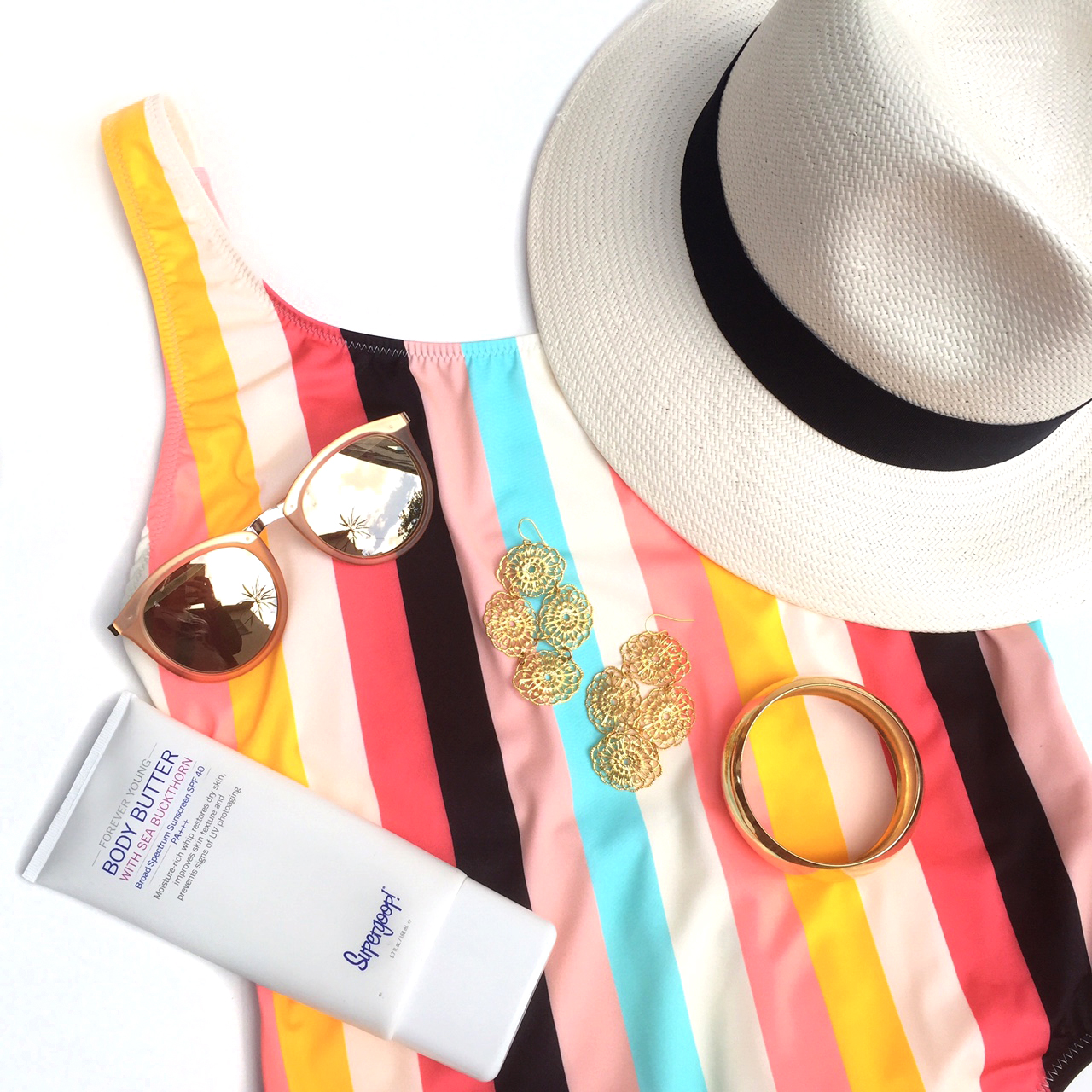 Supergoop Body Butter ,  Janna Conner Lace Filigree Earrings  ,   Janna Conner Dome Bangle ,  Le Specs sunglasses ,  Scala Panama Hat  and  Solid & Striped Bathing Suit.