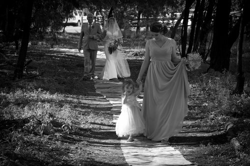 Bridesmaid and flower girl walking along path together.jpg