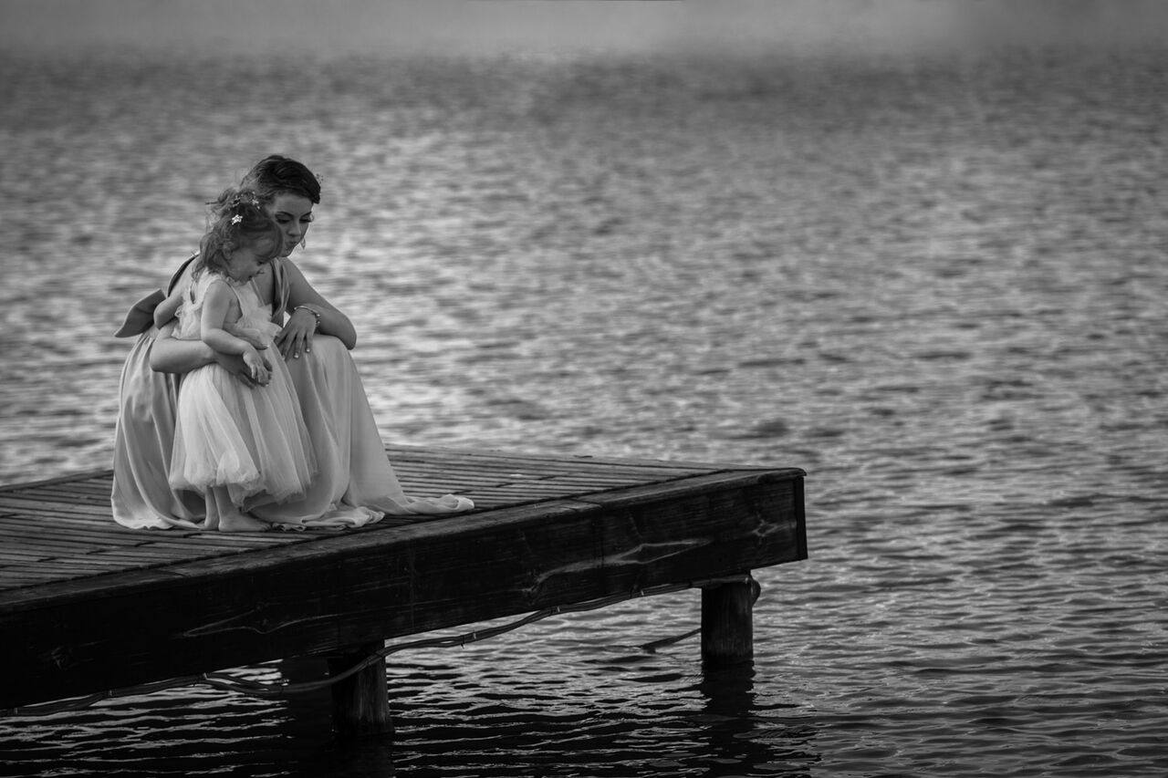 Bridesmaid and flower girl standing on a jetty looking at the water.jpg