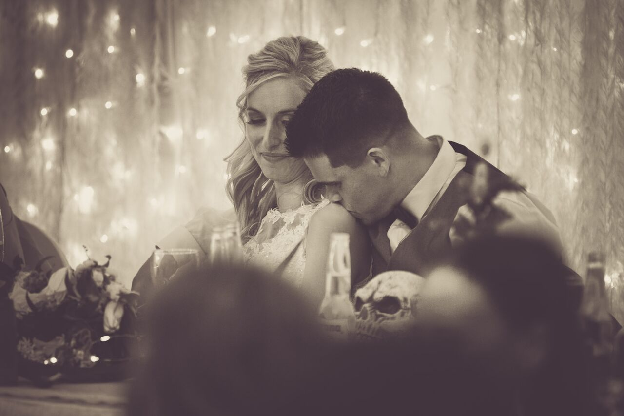 Candid shot of bride and groom sitting together at reception.jpg