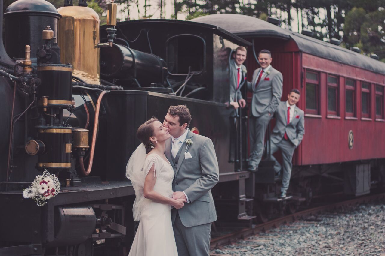 Bride and groom standing in front of steam engine with groomsmen in the background.jpg