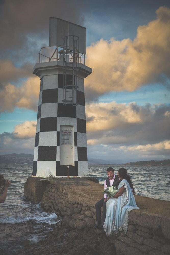 Bride and groom sitting on rocky path towards lighthouse.jpg