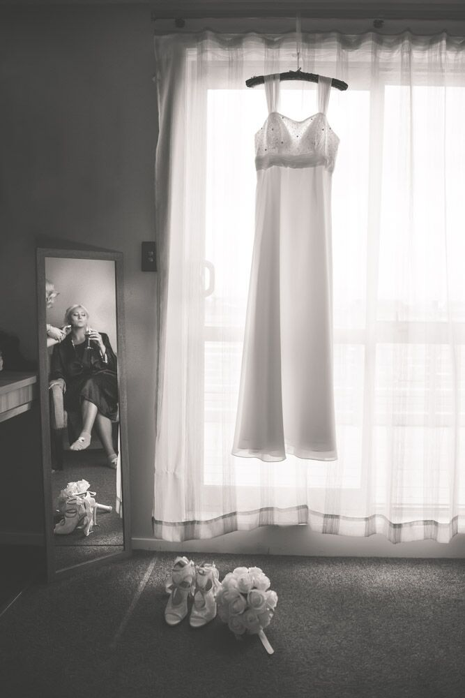 Wedding dress hanging in window while bride gets ready.jpg
