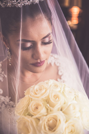 Close up of bride holding bouquet of roses with veil covering her face.jpg