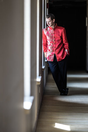 Groom leaning against a wall in a hallway in a traditional Chinese wedding suit.jpg