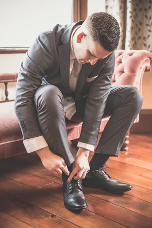 Groom tying his shoes on hiw wedding day.jpg