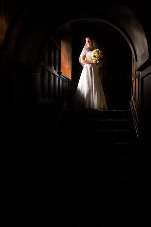 Dramatically lit photo of bride walking down stairs in her wedding dress.jpg