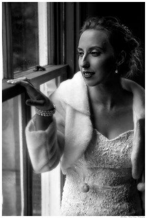 Waist up shot of bride in her wedding dress standing by a window.jpg
