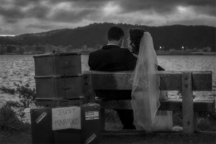 Bride and groom sitting on bench seat along the wellington waterfront in dramatic lighting.jpg