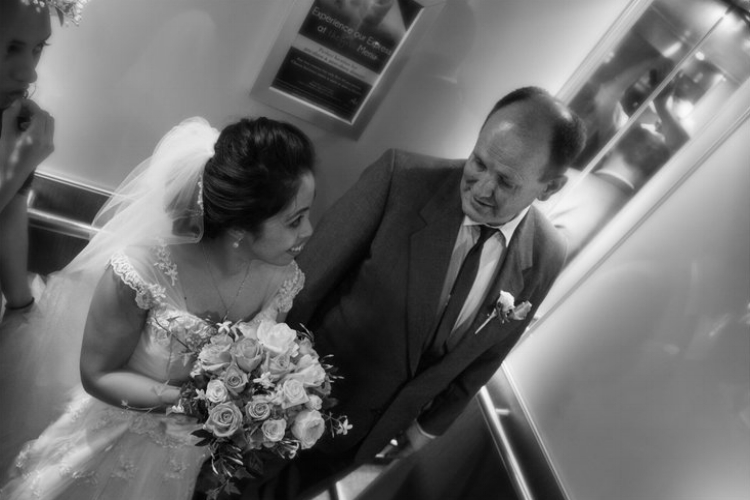 Dutch angle photo of bride and father of the bride standing together in an elevator.jpg