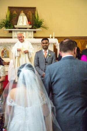 Groom smiling as his bride walks down the aisle.jpg