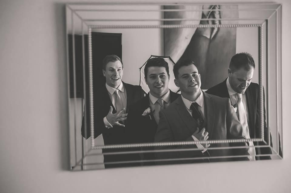 Reflection of groom and groomsmen in mirror.jpg