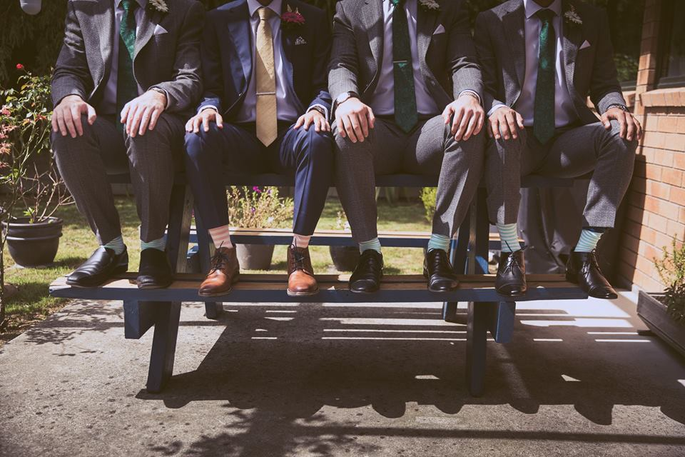 Groom and groomsmen sitting on picnic table with hands on their knees.jpg