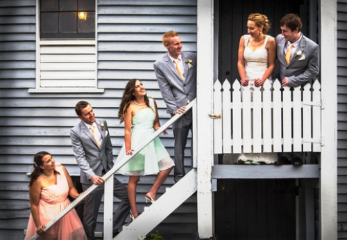 Bride and groom at the top of a staircase with groomsmen and bridesmaids standing on the steps.jpg