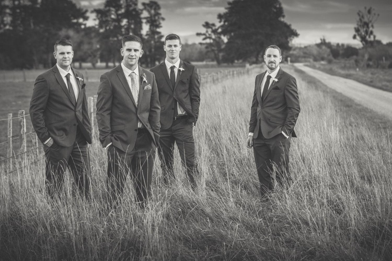 Grooms and groomsmen standing in a field.jpg