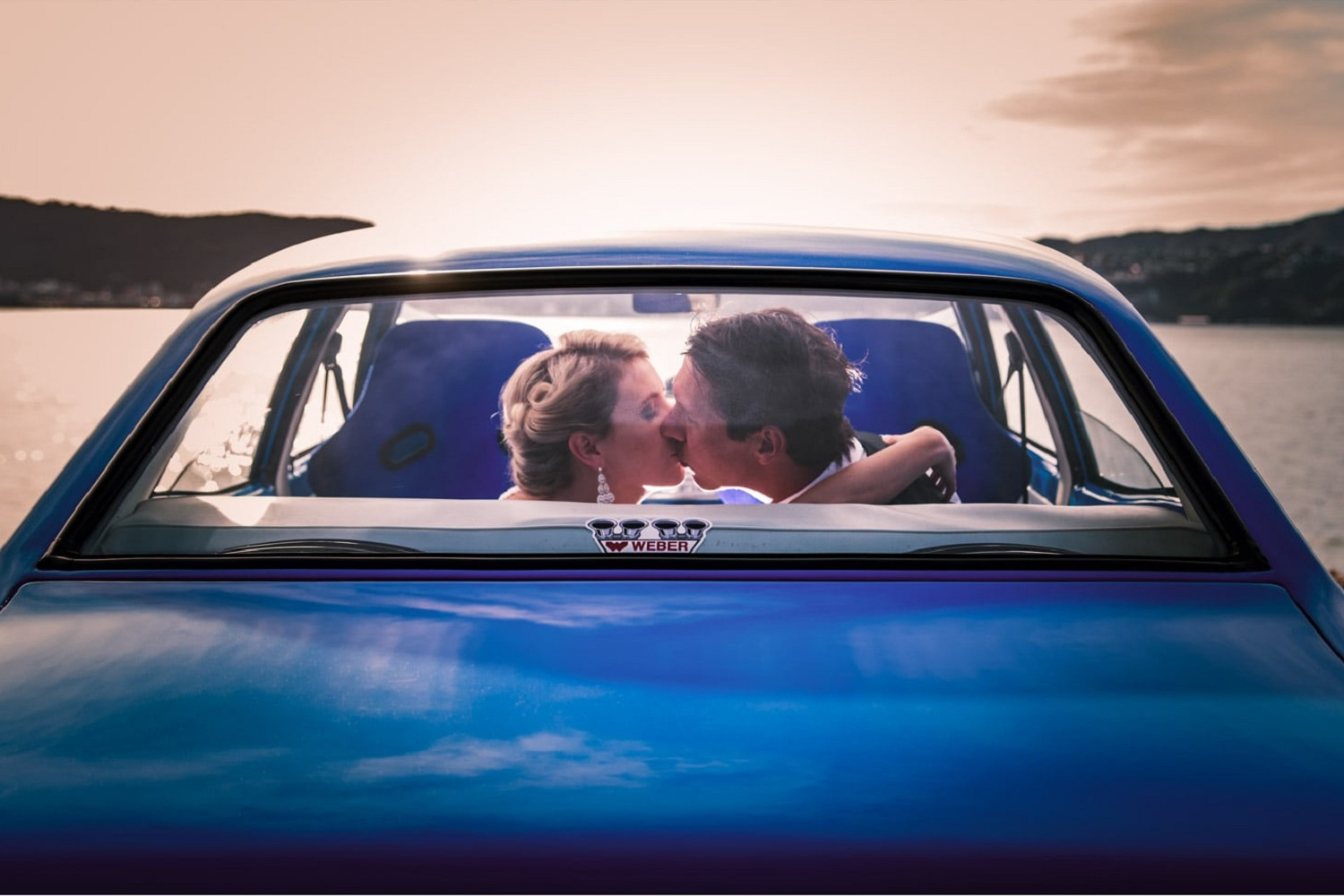 Bride and groom kissing in blue vintage car.jpg