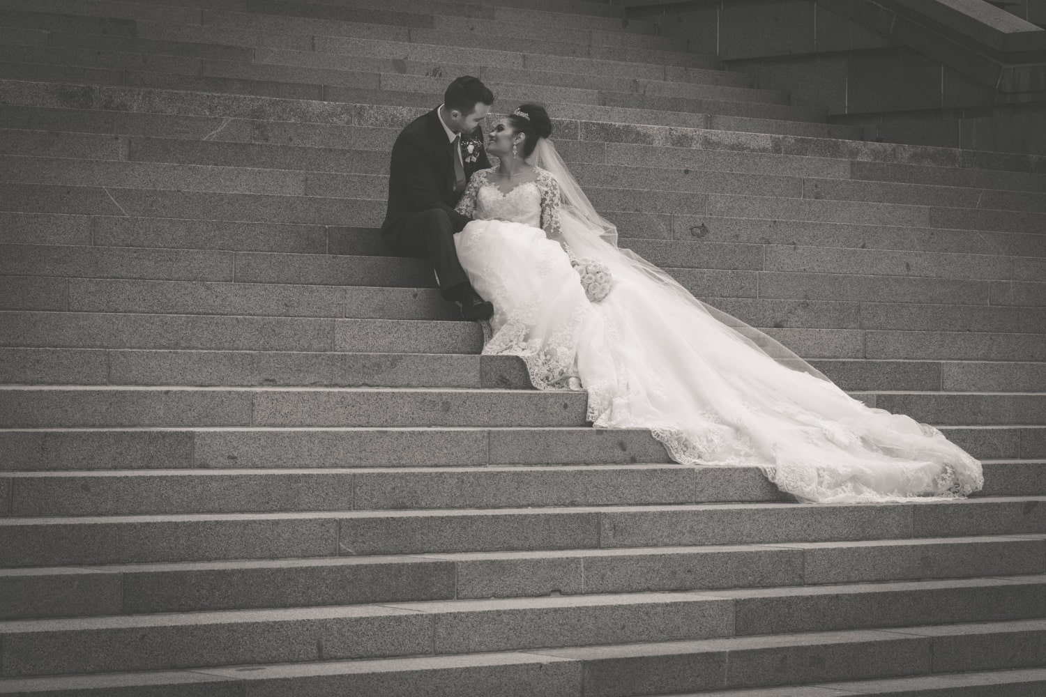 Bride and groom sitting on steps with brides train trailing down.jpg