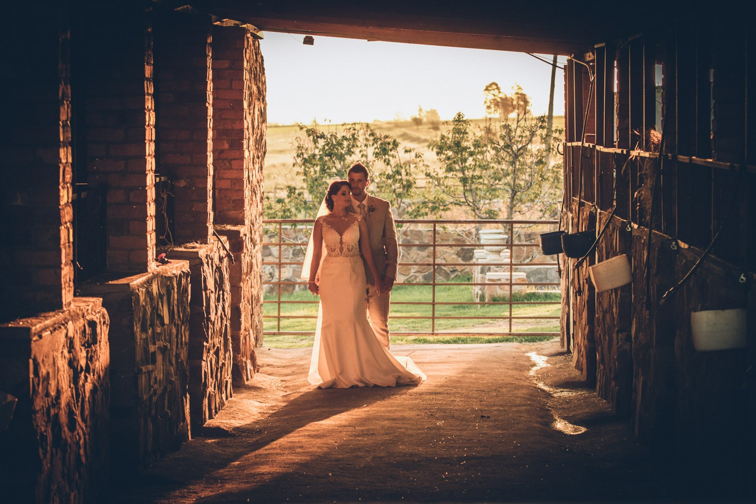 Bride and groom standing in stables.jpg