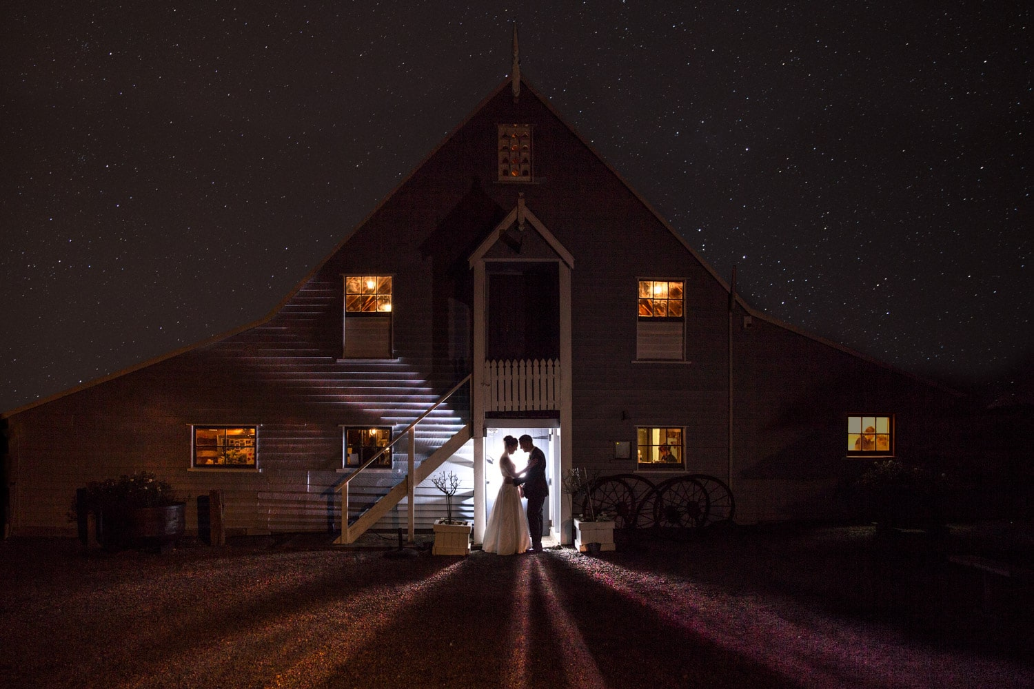 Bride and groom standing together in barn doorway under stars.jpg