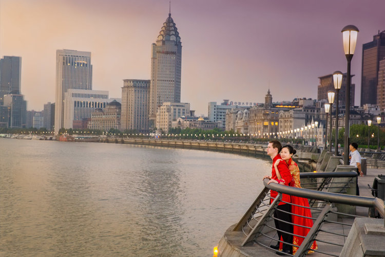 Photo of bride and groom posing againt ballastrade over looking the water with city skyline in the background.jpg