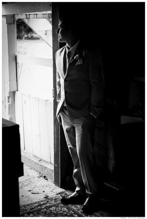 Half dark half light photo of groom standing in doorway.jpg