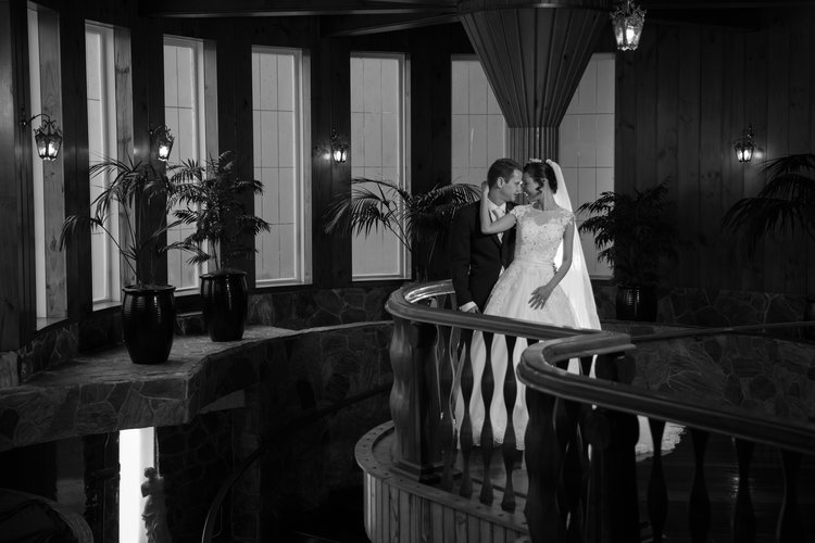 Bride and groom standing on a balustrade in an ornate and elegant hall.jpg