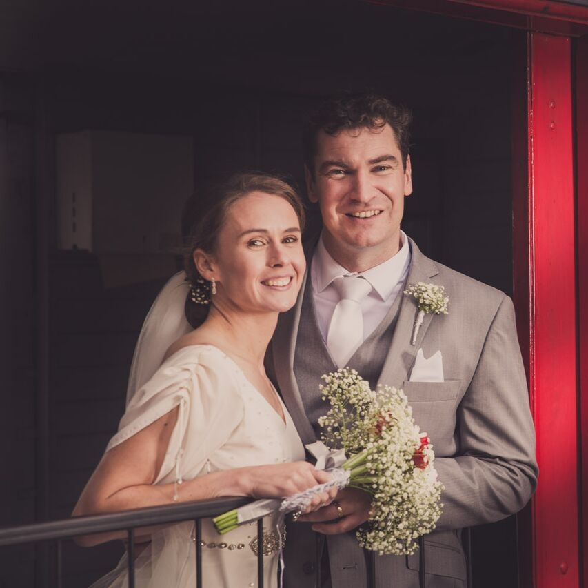 Close up of bride and groom standing on steam engine.jpg