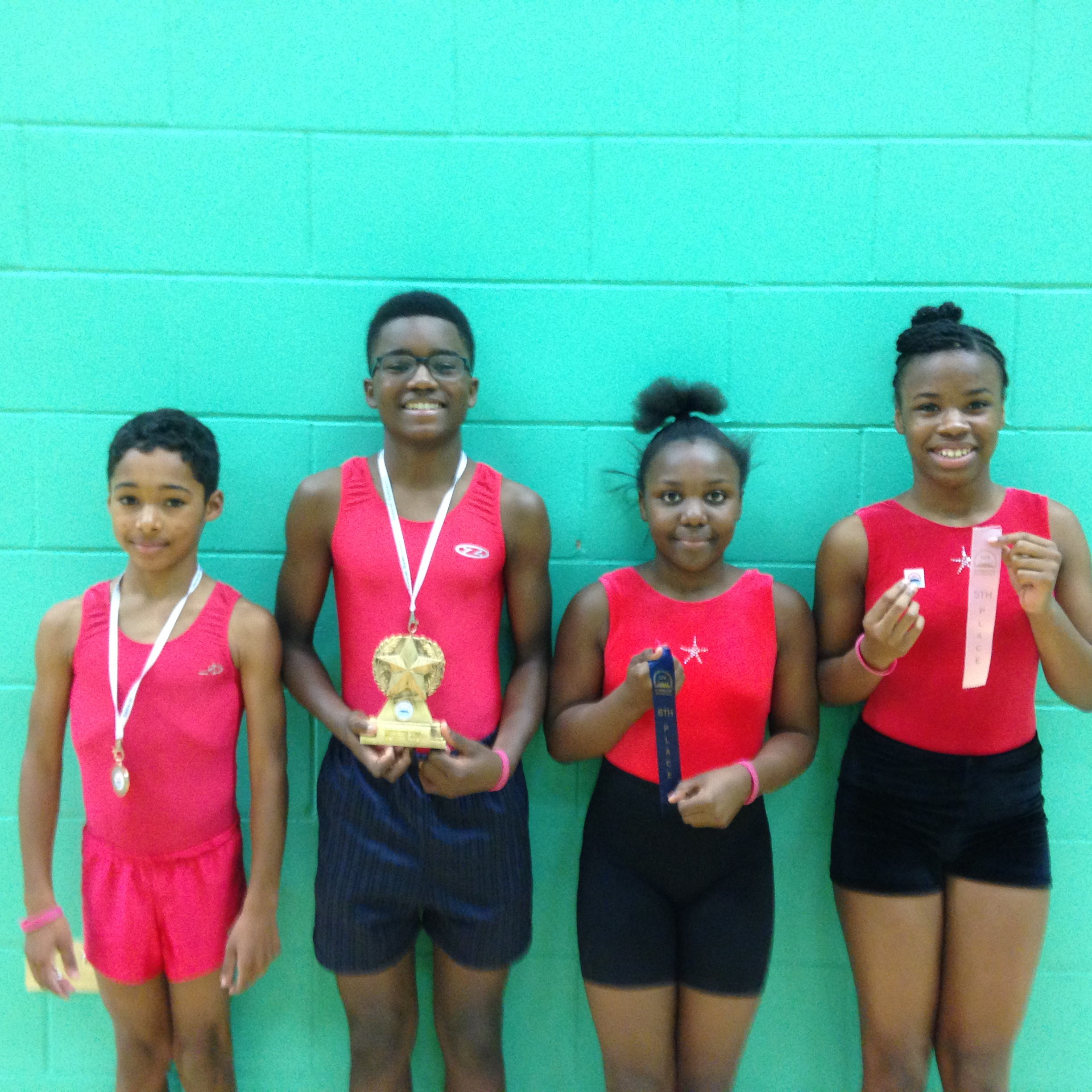 Reuell Nathan Karmae and Nevaeh with medals ribbons trophies and pins.JPG