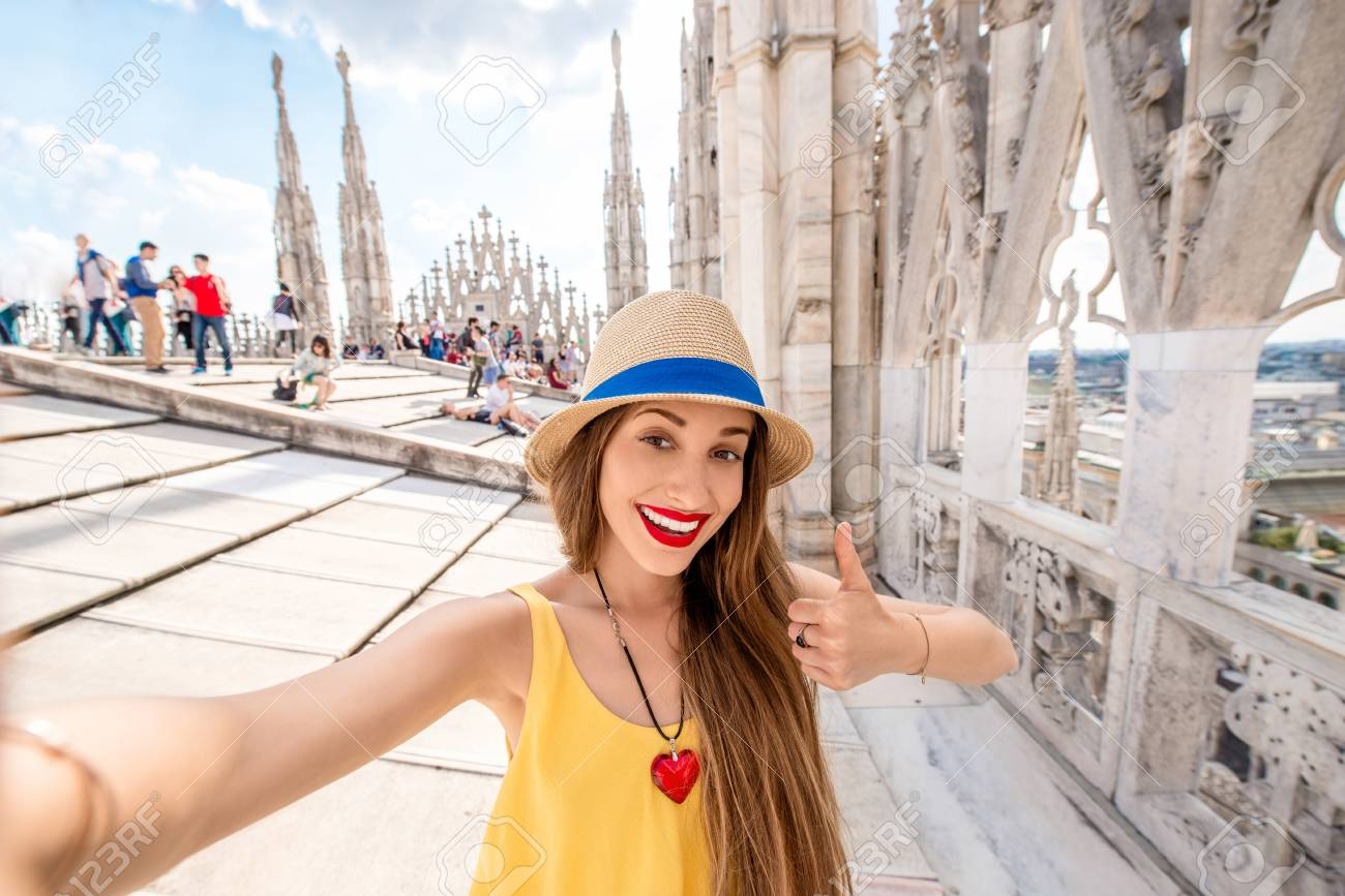62790116-young-and-happy-female-traveler-making-selfie-portrait-standing-on-the-rooftop-of-the-famous-duomo-c.jpg