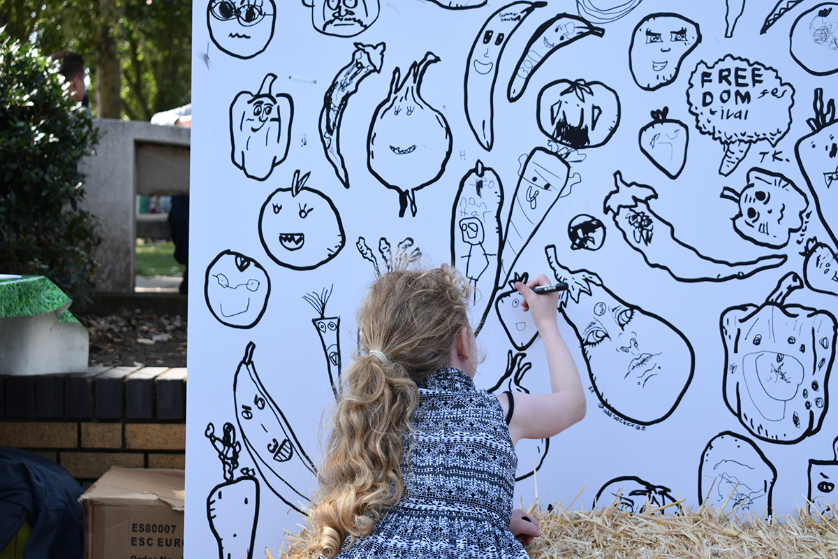 Children added faces to the vegetables as part of the large mural