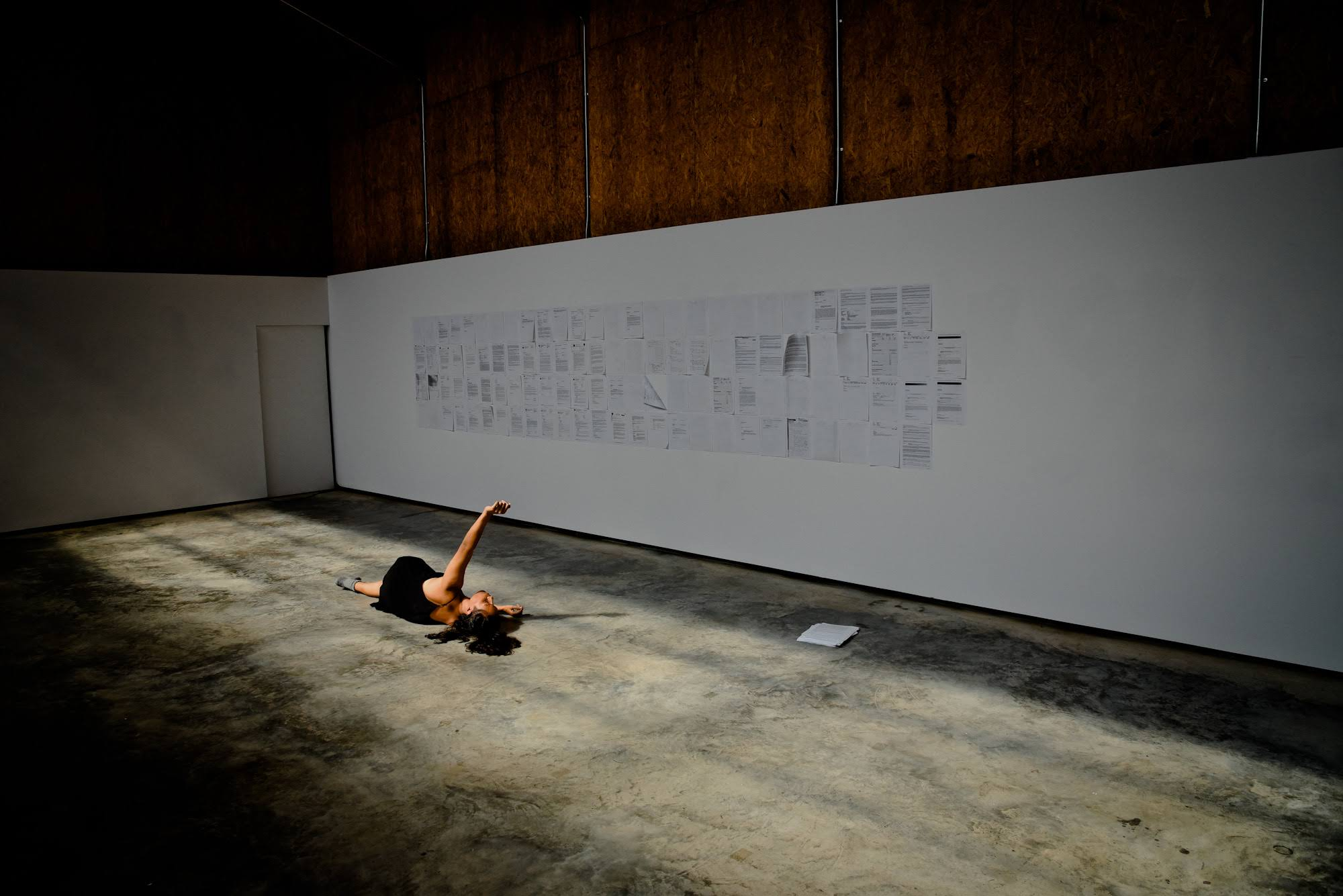 Image from July 2018, Denniston Hill. Pelenakeke is lying on the floor, on her side, arm outstretched above her, dancing in front of an installation of her medical record. Photo credit: Vladimir Radojicic