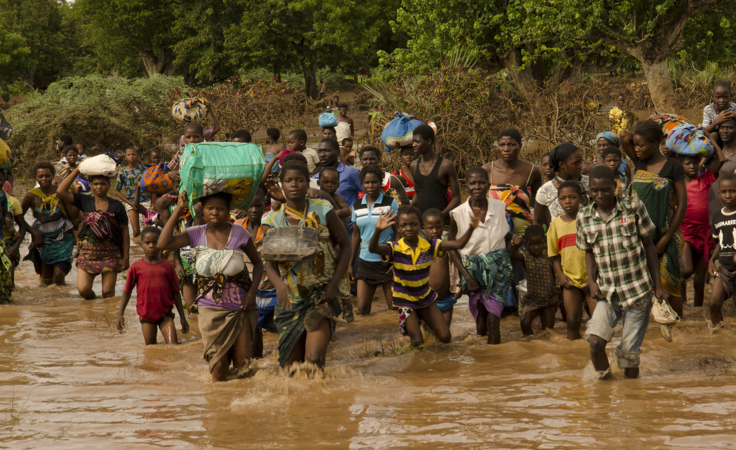 Villagers rush towards an army boat - among thousands that have been evacuated
