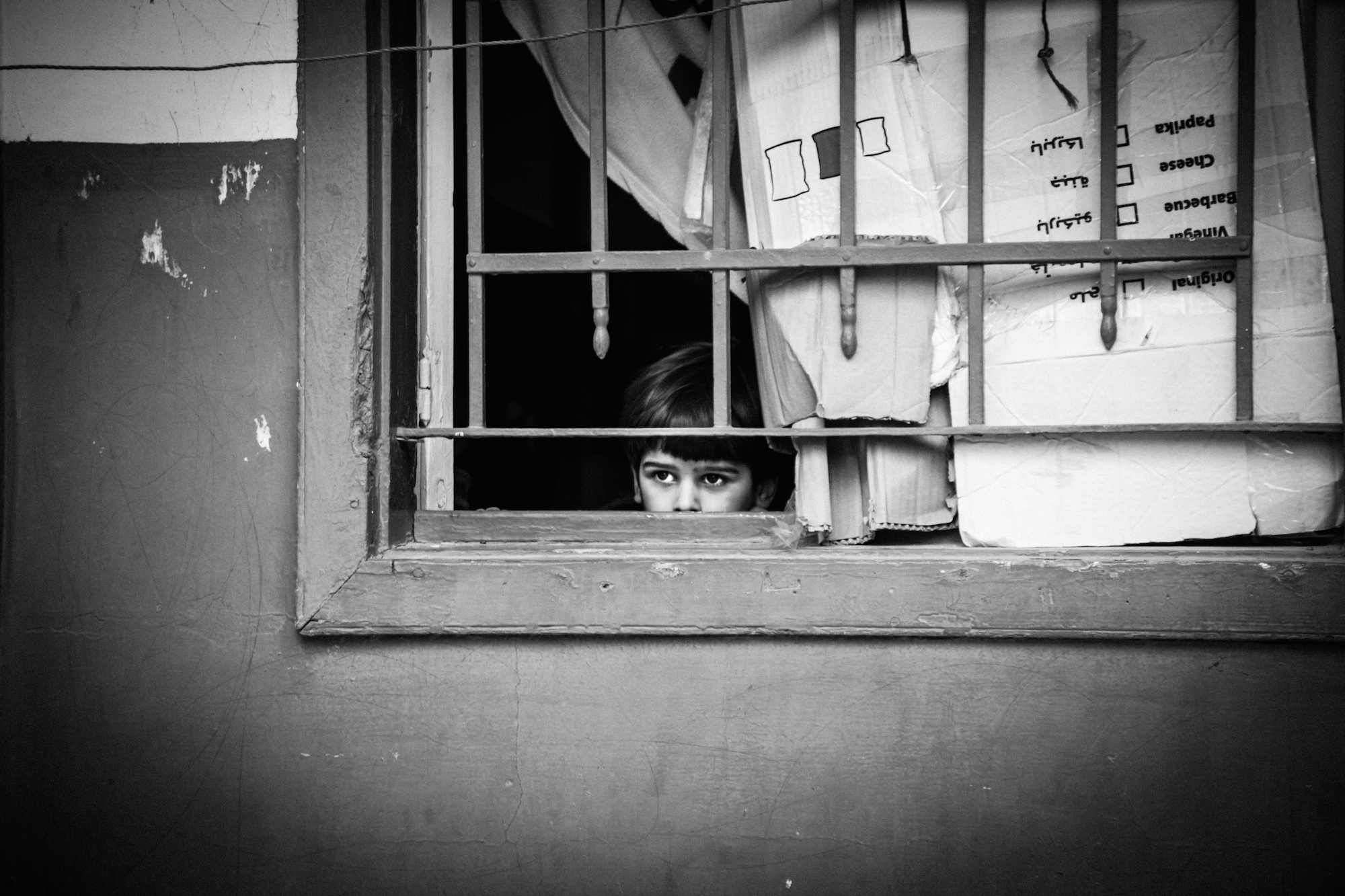 A young Syrian child peers out of a window in Lebanon's Beka'a Valley. Christina Malkoun/IRIN