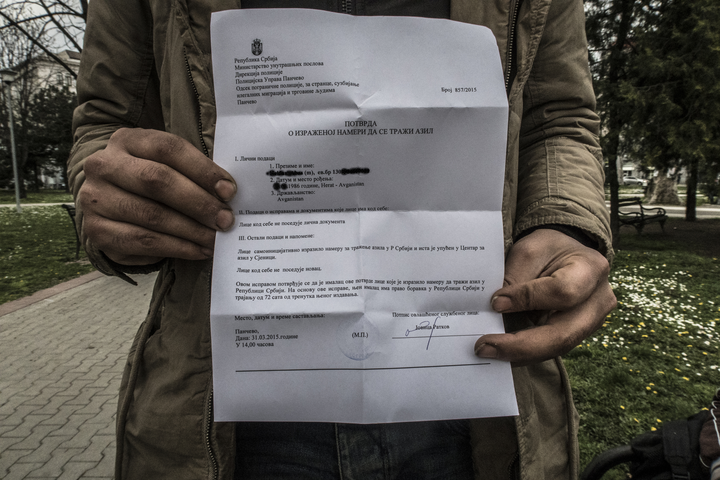 An asylum seeker holds up the registration paper issued by Serbian police that will secure him a place at a centre for asylum-seekers in Sjenica.