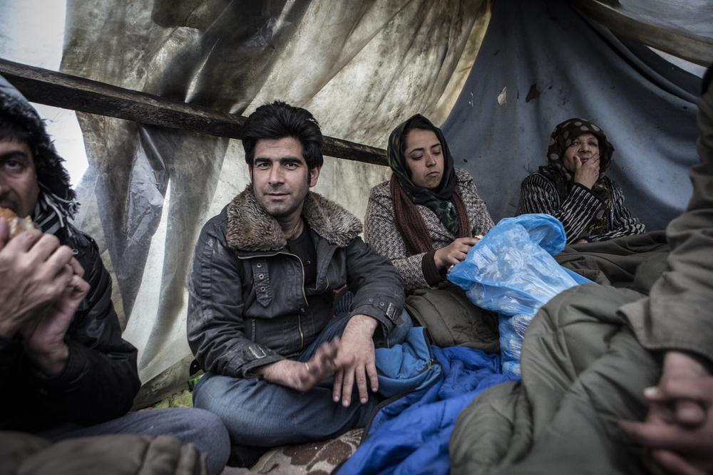 لاجئون أفغان يجلسون تحت غطاء بلاستيكي في سوبوتيتسا ويتناولون الشطائر التي تبرع بها أحد السكان المحليين