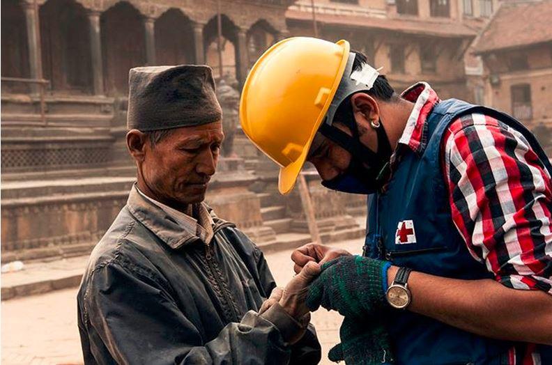 عامل إغاثة من الصليب الأحمر يعالج رجلاً نيبالياً مصاباً