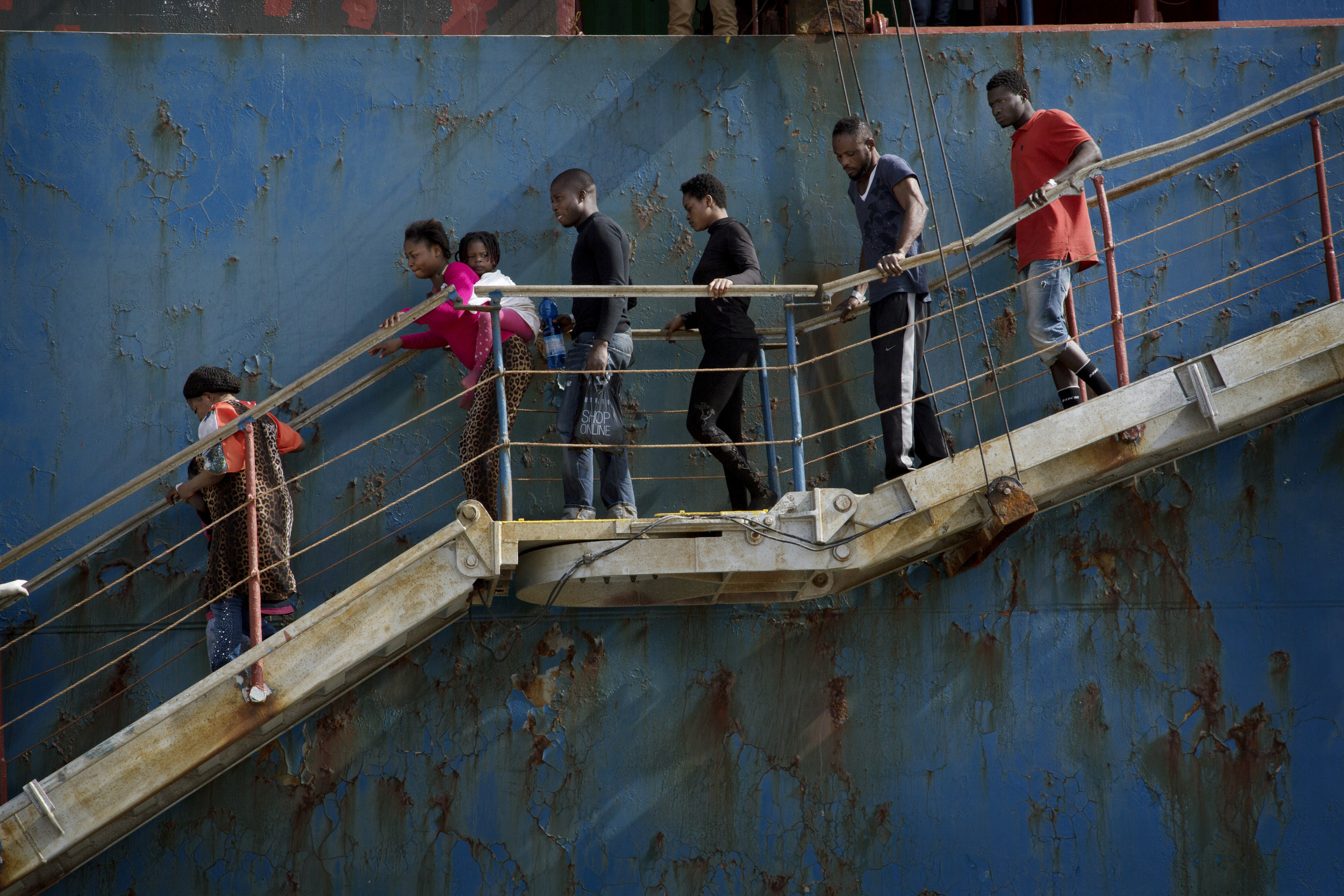 Rescued migrants disembark from the cargo ship that rescued them.