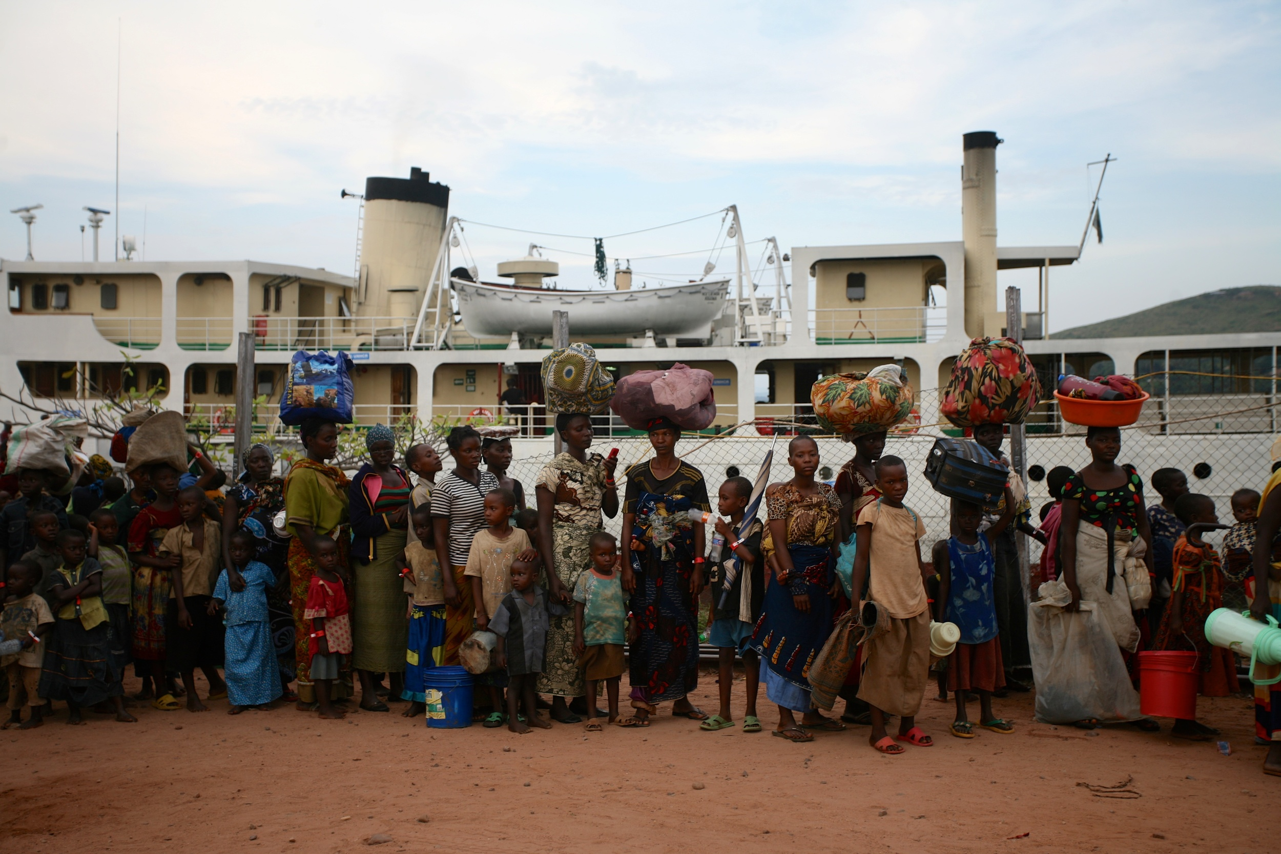 Once Burundian refugees arrive in Tanzania, theyqueue for transportto the temporary transit camp at the Lake Tanganyika Stadium.