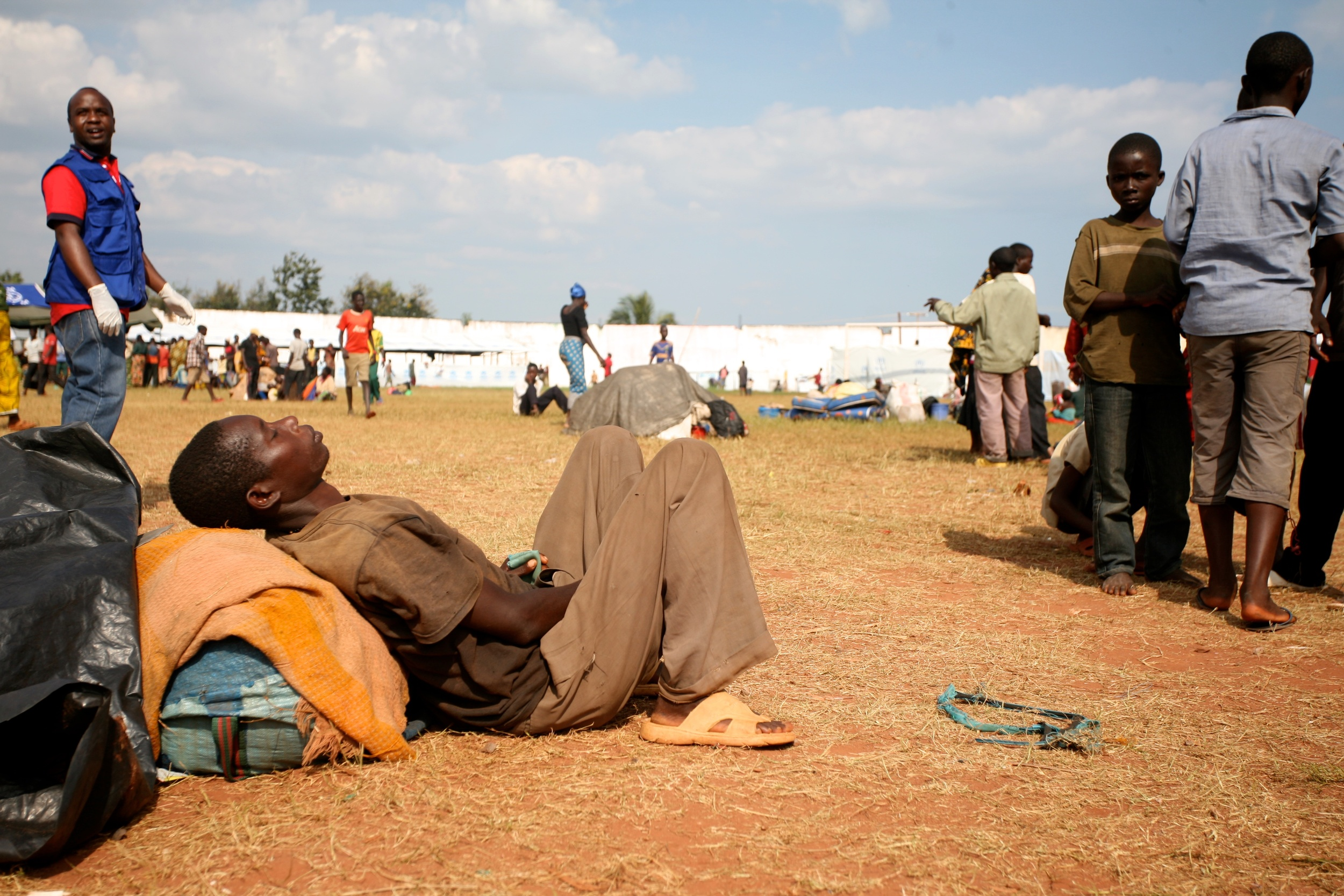 A Burundian refugee dozes in the sun at Lake Tanganyika Stadium in Kigoma, which has beenturned into a transit site for the refugees