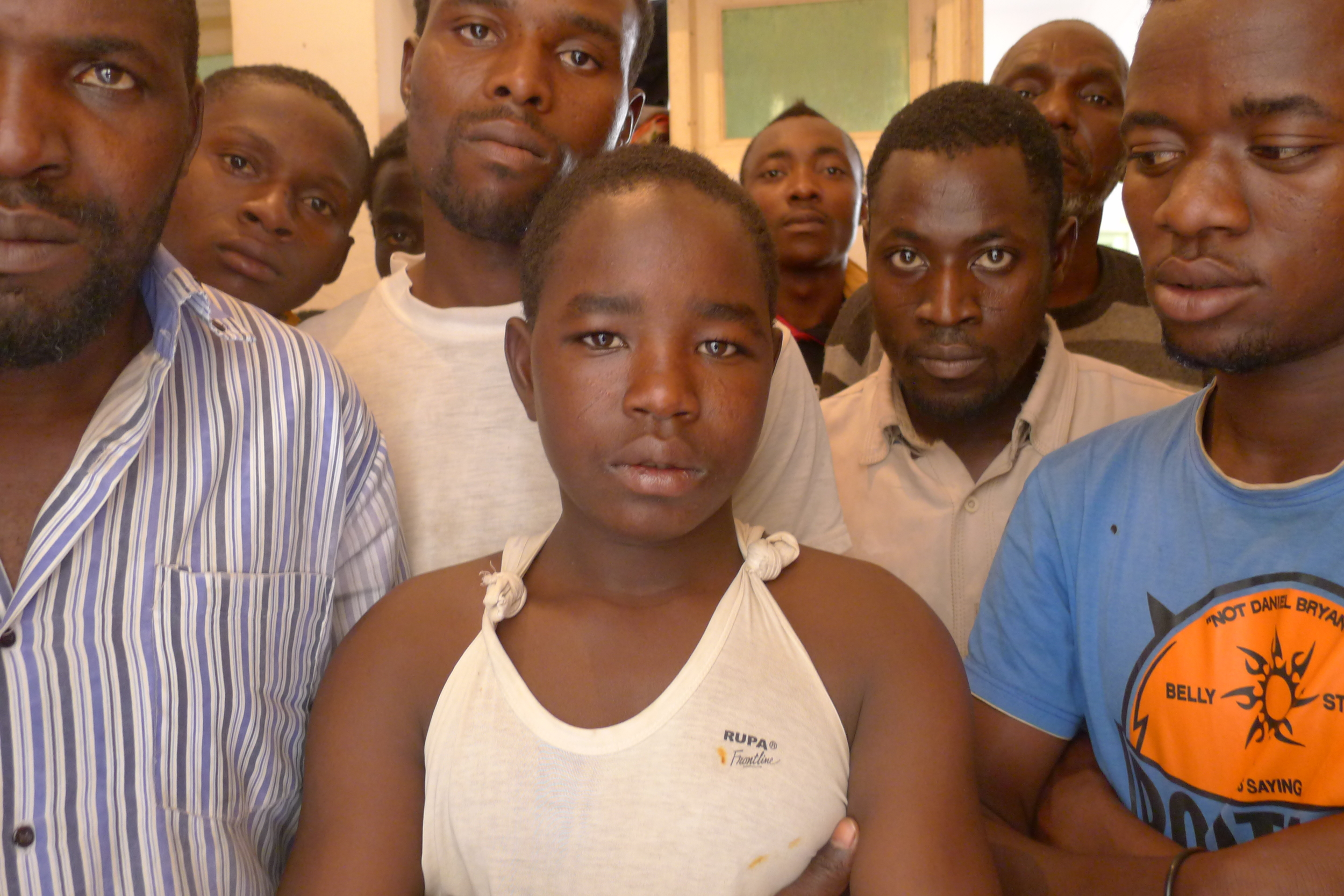 Malti, Krareem's youngest detainee, flanked by some of the adults he is locked up with.