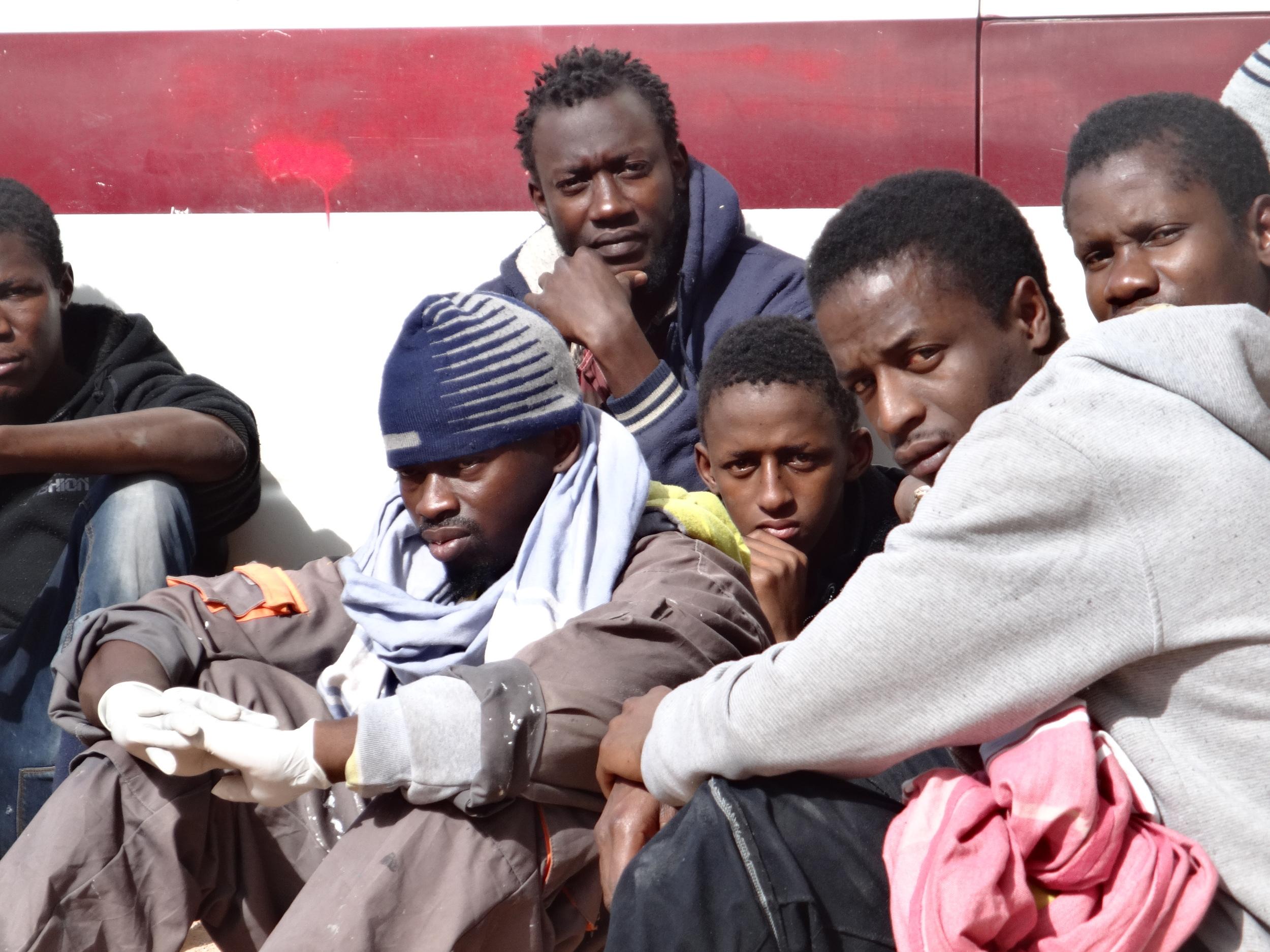 Des migrants rassemblés à l'extérieur du centre de rétention