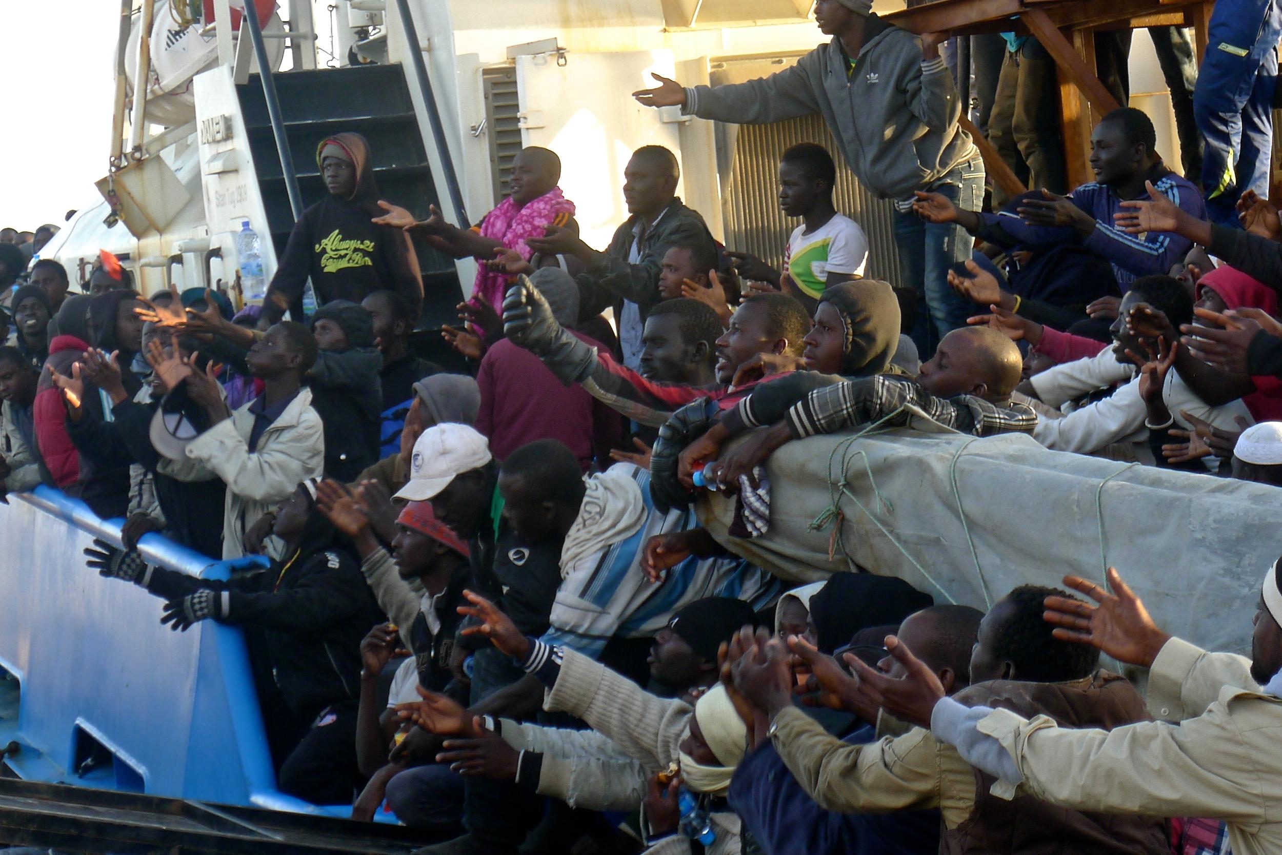 Plus de 400 migrants interceptés par les gardes-côte de Misrata alors qu'ils voyageaient dans quatre bateaux pneumatiques tendent les bras pour attraper des bouteilles d'eau qui leur sont jetées depuis la rive. Nombre d'entre eux ont ensuite été transférés au centre de rétention de Krareem.