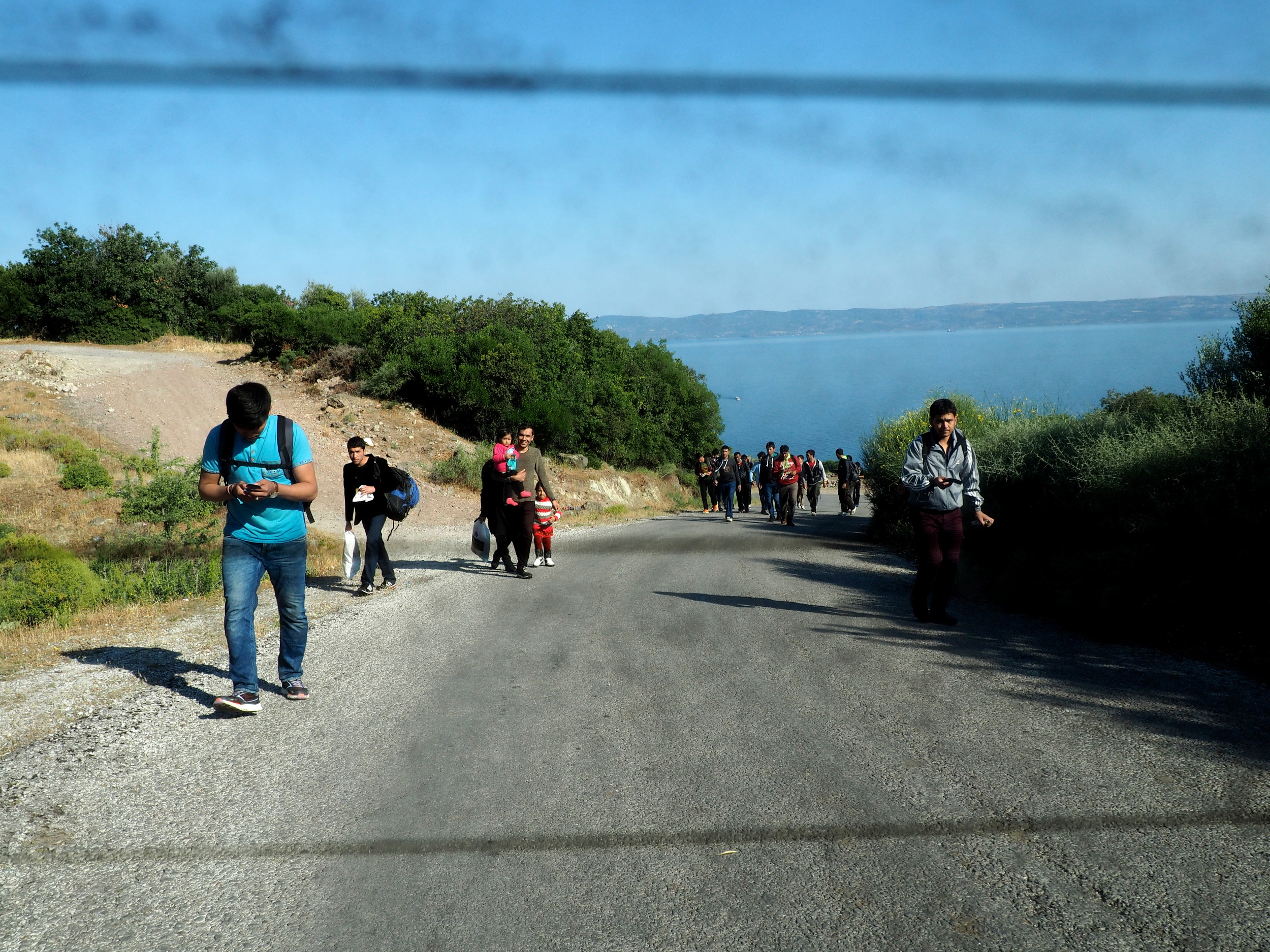 Migrants begin the 60 kilometre trek from Skala Sykaminias to Mytilene. Locals who offer them lifts risk being charged with human smuggling.