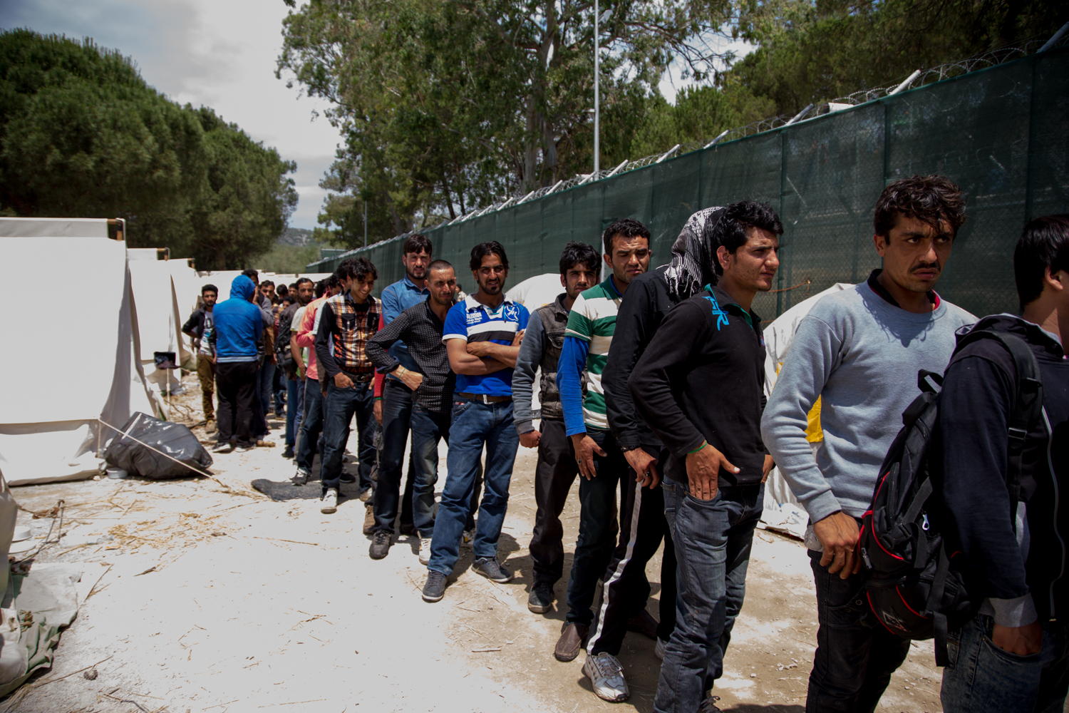 Migrants queue for tea at Moria detention centre