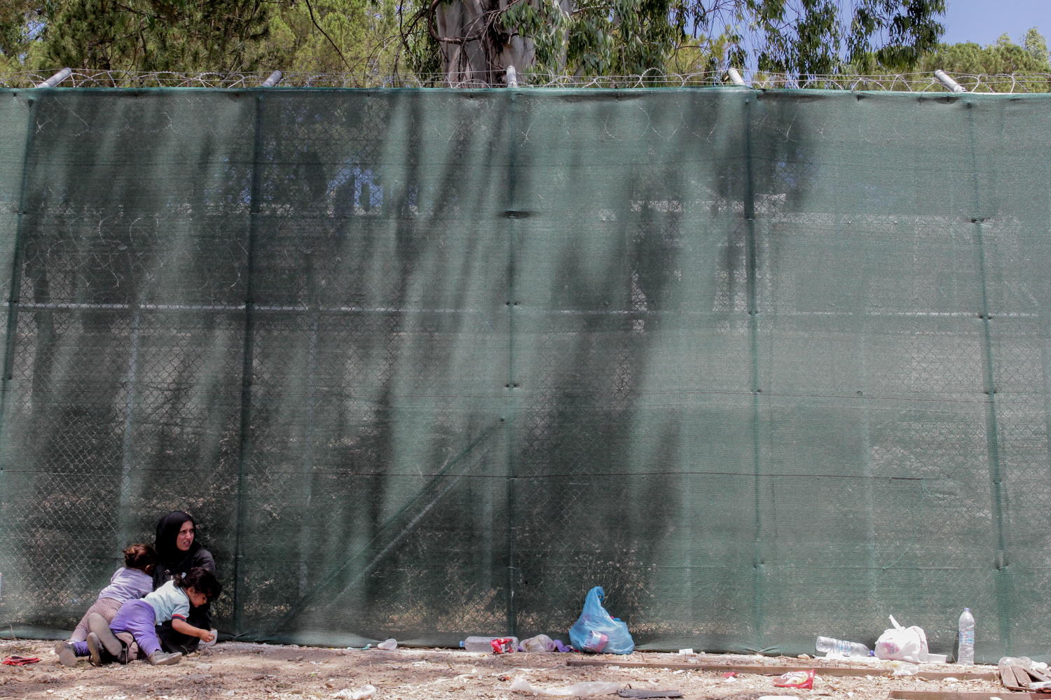 A woman and her two young children try to find some shade at Moria detention centre