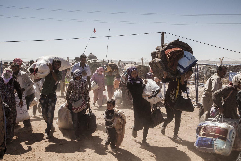 لاجئون أكراد سوريون يعبرون الحدود من سوريا إلى تركيا، بالقرب من بلدة كوباني. وقد حول الصراع السوري، الذي بدأ في عام 2011، البلاد إلى أحد أكبر دوافع النزوح في العالم. (إ. بريكيت/مفوضية الأمم المتحدة لشؤون اللاجئين)