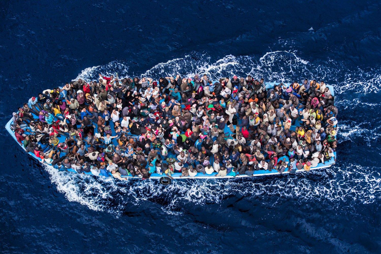 صورة تبين مئات اللاجئين والمهاجرين على متن قارب صيد قبل لحظات من إنقاذهم بواسطة البحرية الإيطالية كجزء من عملية بحرنا في يونيو 2014. وقد حدثت زيادة كبيرة في عدد اللاجئين الذين يبحثون عن الأمان من خلال القيام برحلات بحرية خطرة، بما في ذلك عبر البحر الأبيض المتوسط (ماسيمو سيستيني/خفر السواحل الإيطالي)