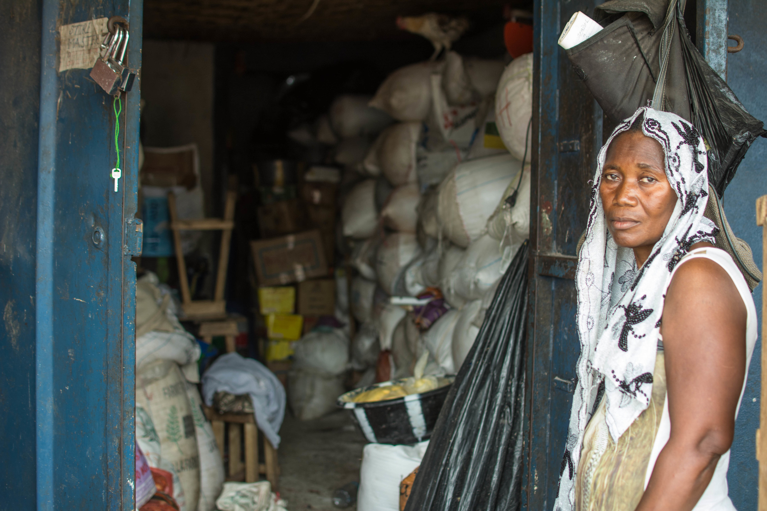 Hannah Kamanda stands outside her storehouse in Freetown, where sacks of gari have begun to pile up. Since Ebola came, she has had difficulty selling her stock.