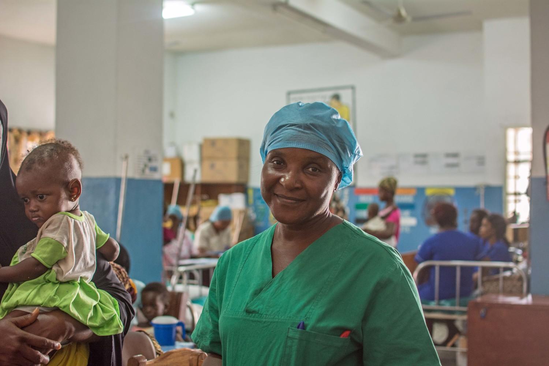 الممرضة لوسي م. م. كوكر تعالج طفلاً يعاني من سوء التغذية في مستشفى كوتيج في فريتاون.